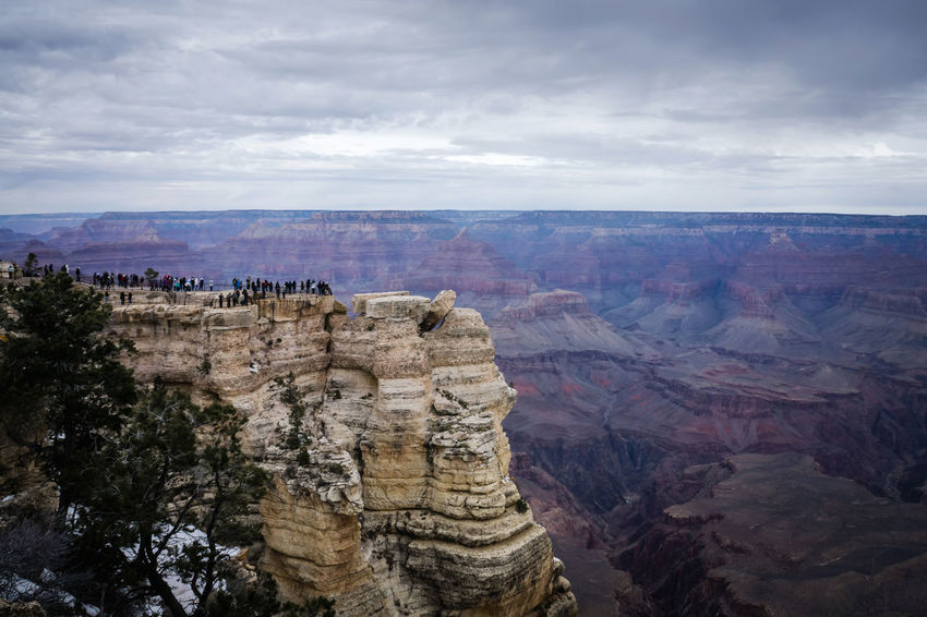 Tourists on Mather Point in Grand Canyon National Park. Beauty In Nature Cliff Desert Eroded Extreme Terrain Famous Place Geology Grand Canyon Idyllic Landscape Mather Point Mountain Nature Physical Geography Remote Rock Rock - Object Rock Formation Rocky Mountains Scenics Sky Tourism Tranquil Scene Tranquility Travel Destinations