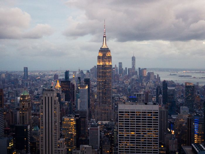 Illuminated empire state building surrounded by cityscape against sky at dusk