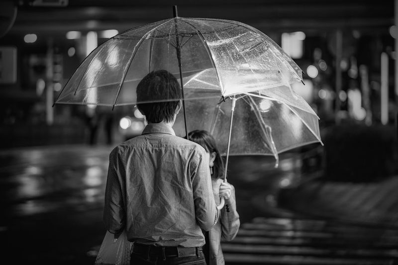 Black & White Tokyo Blackandwhite City Focus On Foreground Illuminated Incidental People Leisure Activity Lifestyles Men Night One Person Outdoors Protection Rain Rainy Season Real People Rear View Security Standing Street Streetphoto_bw Streetphotography Umbrella Wet