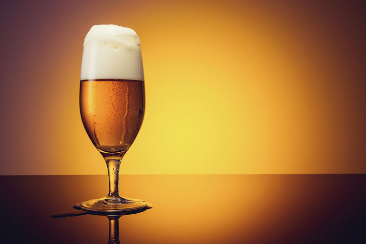 overflowting beer glass against sunset background Beer Beverage Dew Drops Froth Overflow Alcohol Beer - Alcohol Beer Glass Close-up Cold Drink Drink Drinking Glass Foarm Food And Drink Freshness Frothy Drink German Beer Glass Gold Colored No People Pint Glass Reflection Refreshment Sunset
