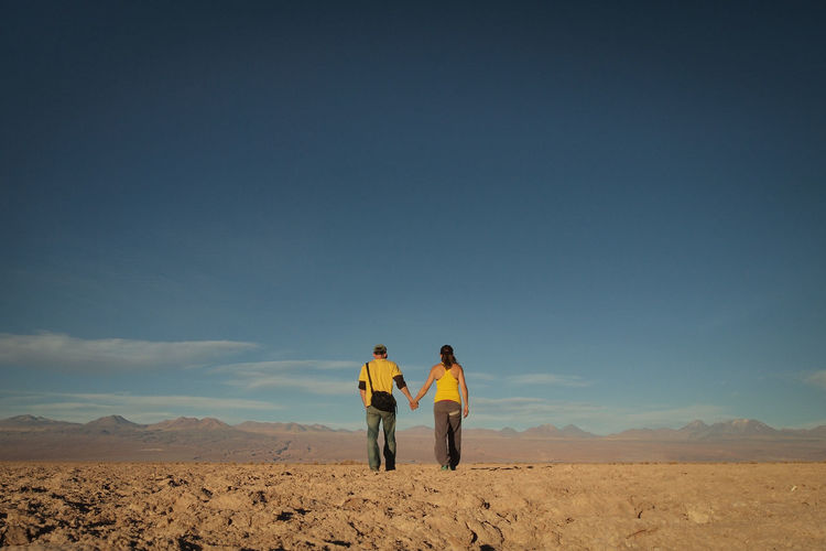 Rear view of couple in desert against sky