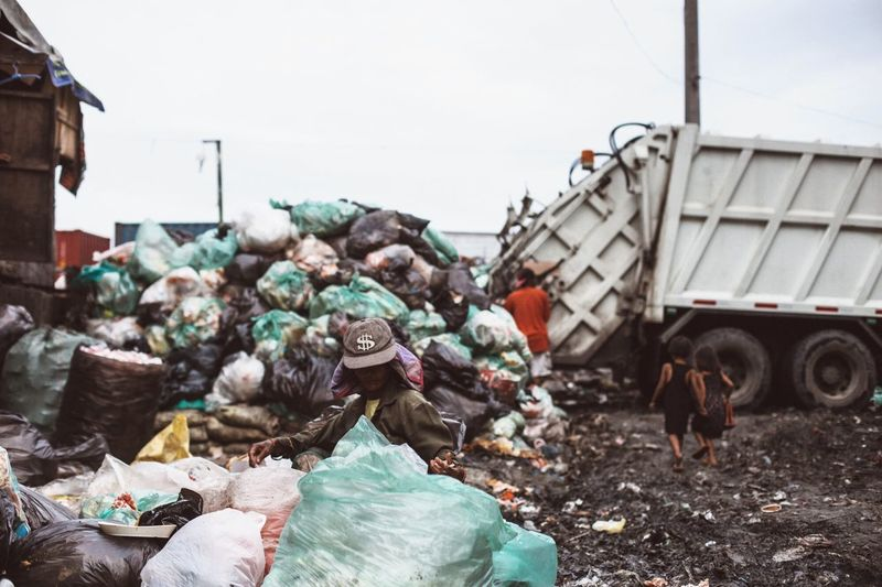 Homeless people searching in garbage heap