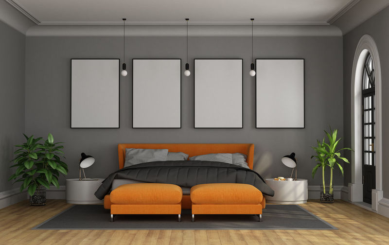 Empty bed against blank frames on wall in bedroom at home