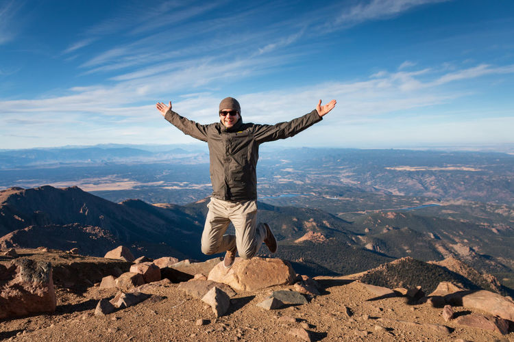 Full length of man jumping in the air and enjoying beeing on top of pikes peak, colorado against sky