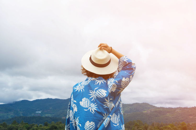 Beauty In Nature Day Hat Leisure Activity Lifestyles Mountain Nature One Person Outdoors People Real People Rear View Scenics Sky Standing Sun Hat Vacations Women