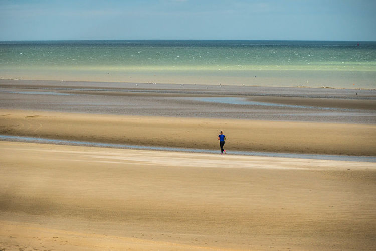 Rear view of woman running on sand at beach
