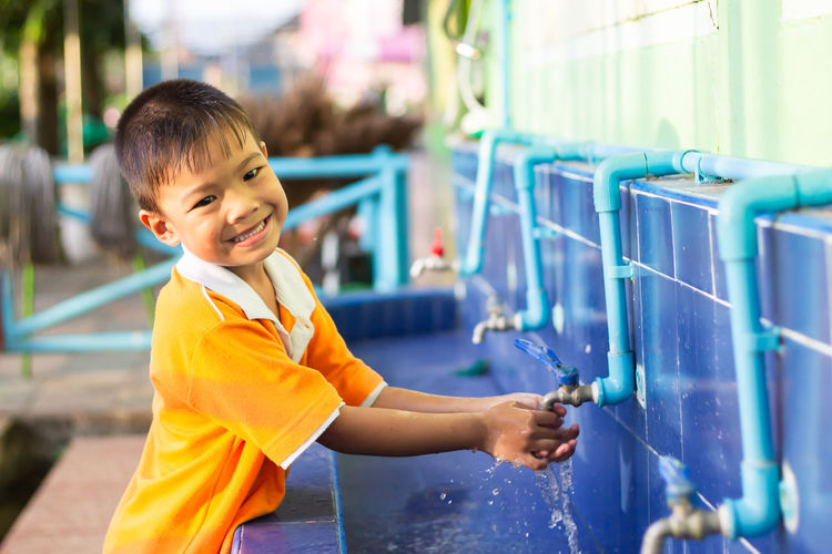 Side view of boy washing hands at park