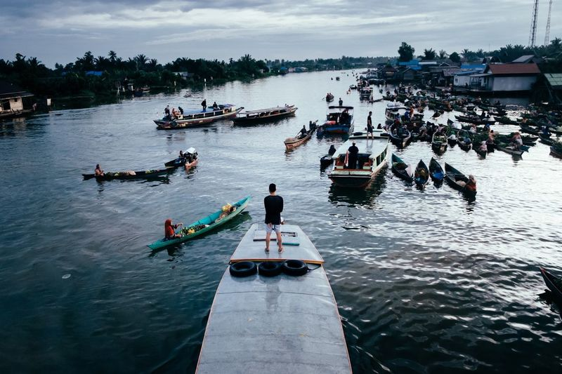 High angle view of man standing on boat deck at floating market in river