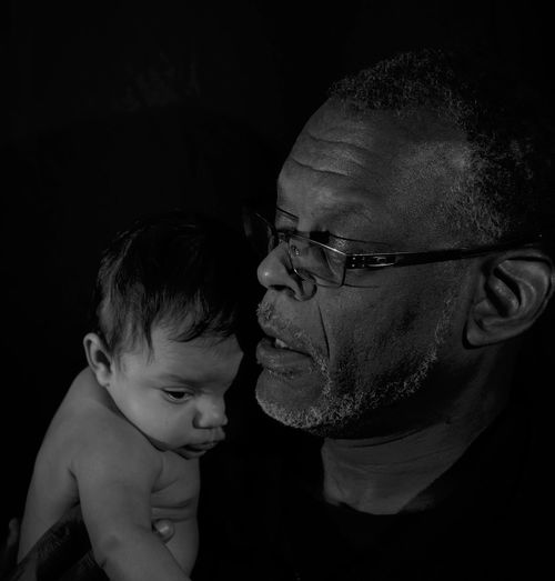 Close-up of father carrying baby boy against black background
