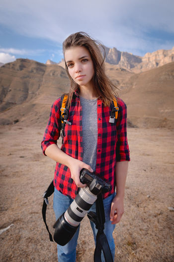 Beautiful young woman standing on land