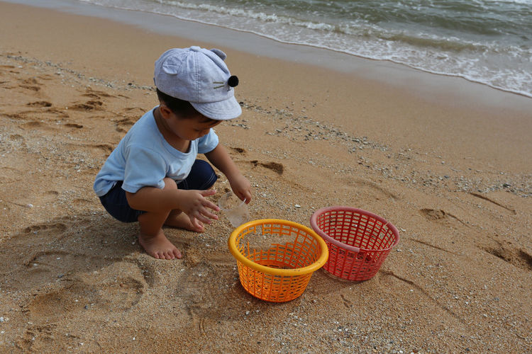 Full length of boy playing on sand at beach