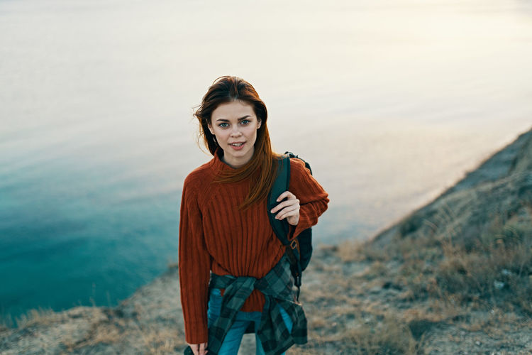 Portrait of young woman standing against sea