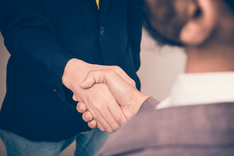 Midsection Of Business Colleagues Shaking Hands