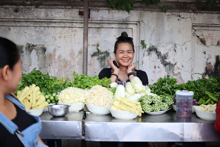 Portrait of smiling woman selling vegetable outdoors