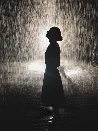 Silhouette woman standing on footpath at night