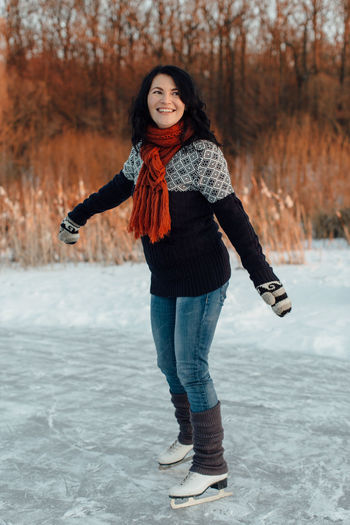 Happy woman learning to ice skate December Frozen Ice Natural Pond Winter Woman Cold Female Gloves Hobby Ice Skater Ice Skating Knitwear Lake Leisure Activity Outdoor Rink Season  Skates Skating Snow Snowy Sport Sunset