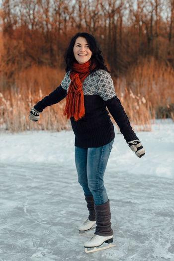 Smiling woman ice-skating on frozen lake