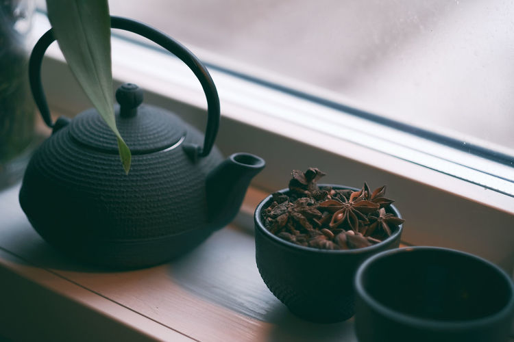 Close-up of spices in cup with teapot on table