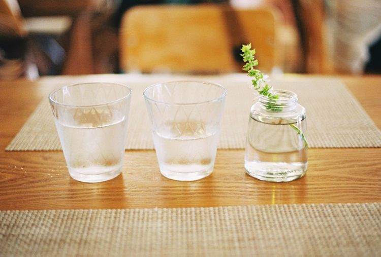 Drinking glasses and jar on wooden table