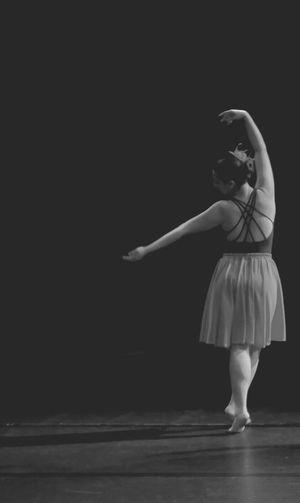 Full length of a female ballerina against black background