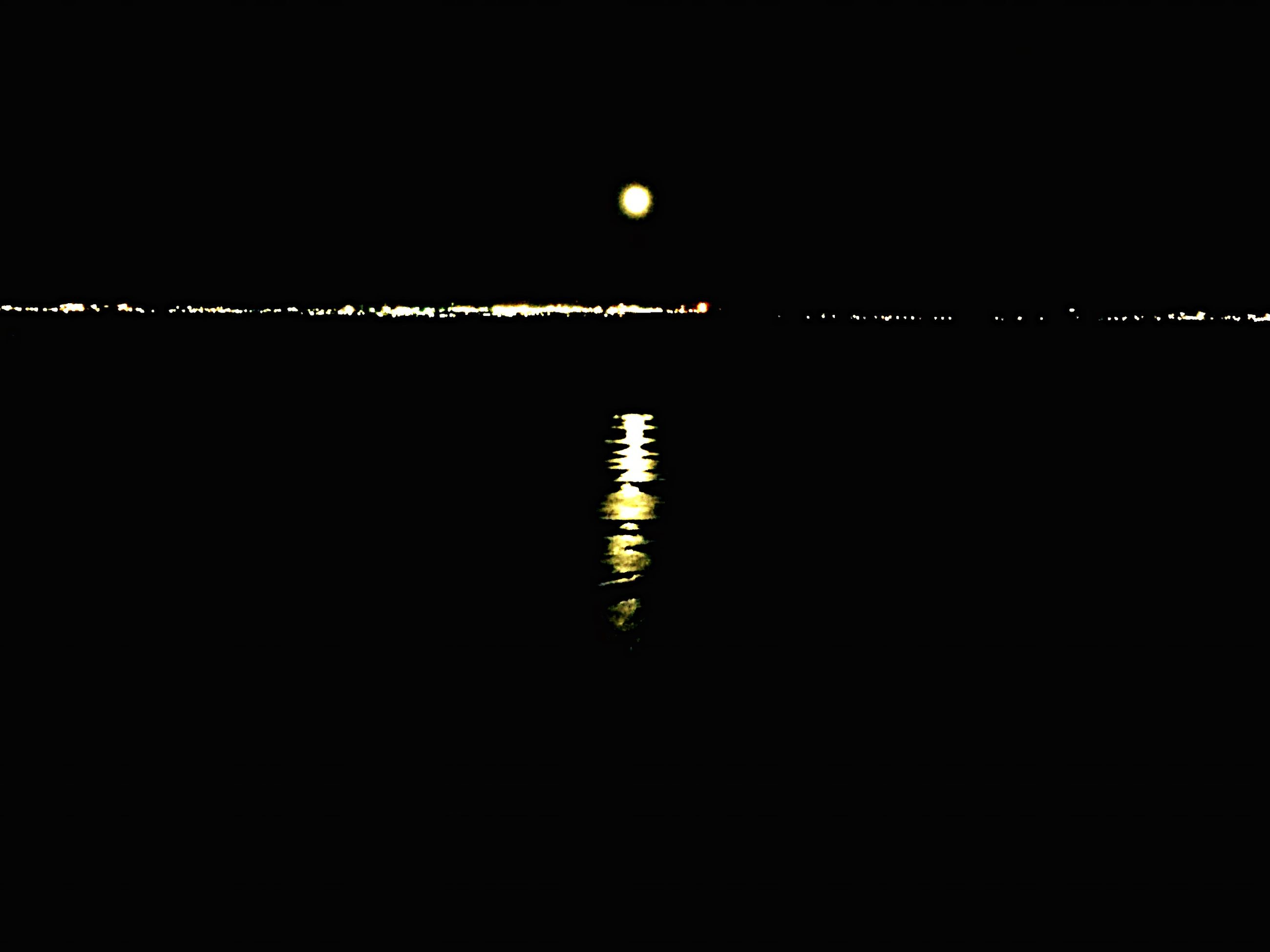 illuminated, night, dark, copy space, reflection, lighting equipment, water, light, in a row, waterfront, clear sky, light - natural phenomenon, glowing, no people, lit, electricity, moon, silhouette, outdoors, sky