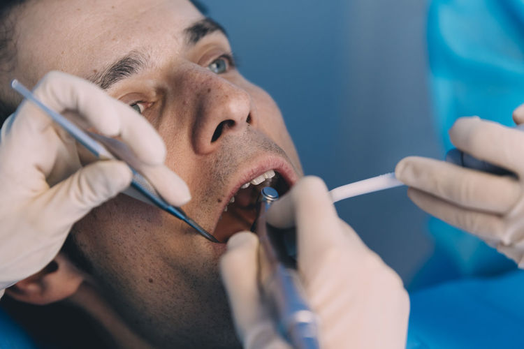 Dentists examining male patient in clinic