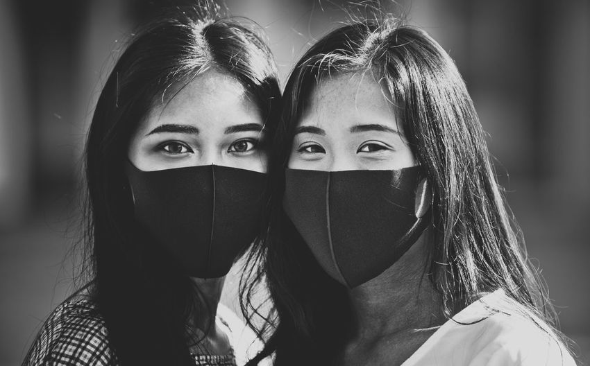 Close-up portrait of friends wearing mask