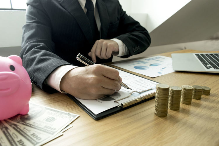 Midsection of businessman writing in graph on table