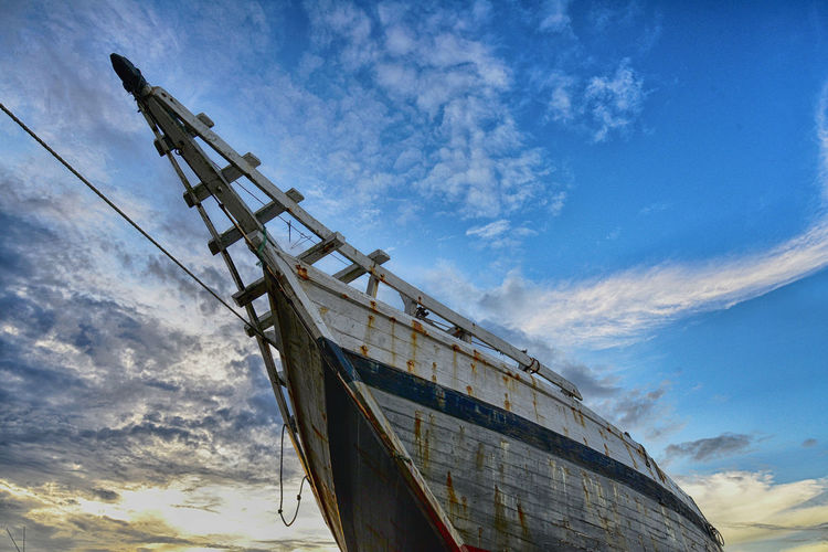 Low angle view of ship against cloudy sky