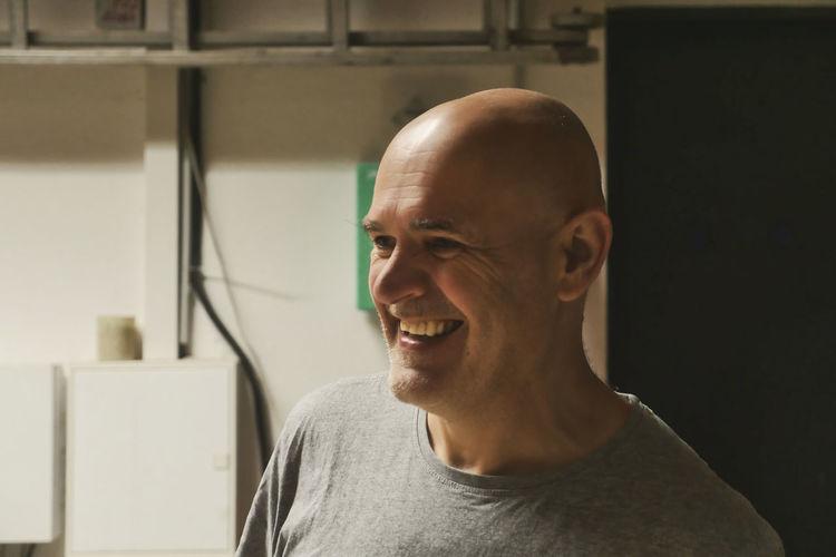 Close-up of smiling man looking away at factory