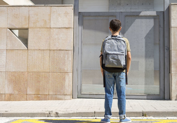 Portrait of a student ( back to school concept ) Student Architecture Backpack Building Building Exterior Built Structure Casual Clothing City Day Full Length Leisure Activity Lifestyles Males  Men One Person Outdoors Real People Rear View School Standing Sunlight Wall - Building Feature