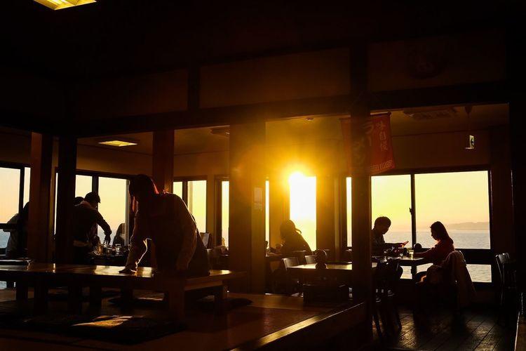 Evening seaside restaurant Silhouette Evening Illuminated Evening Sky Travel Destinations Sunset Sunlight Sunbeam Restaurant Restaurant Decor Seascape Window View