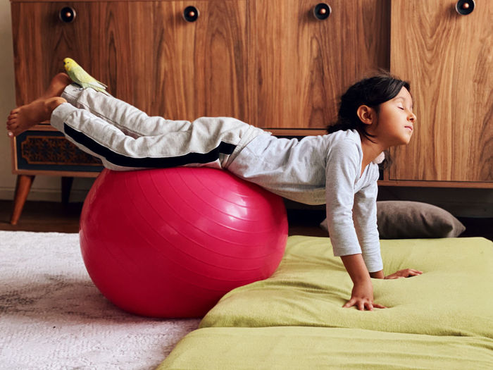 Full length of girl exercising with fitness ball at home