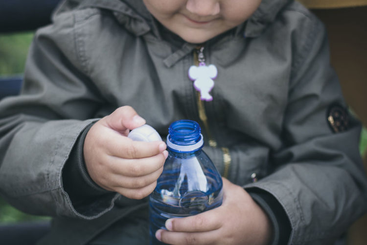 Midsection of girl holding water bottle