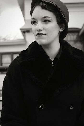 Young woman looking away while standing outdoors