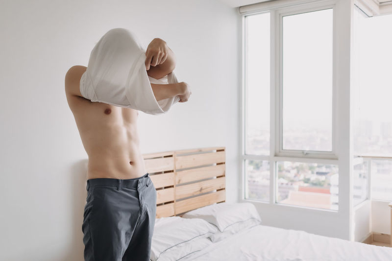 Midsection of shirtless man standing on bed at home