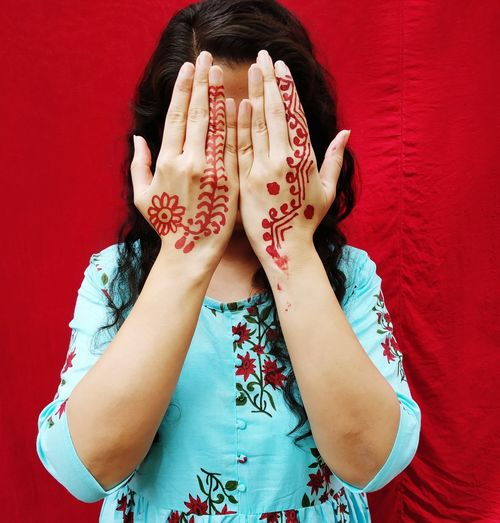 Woman showing henna tattoo against red background