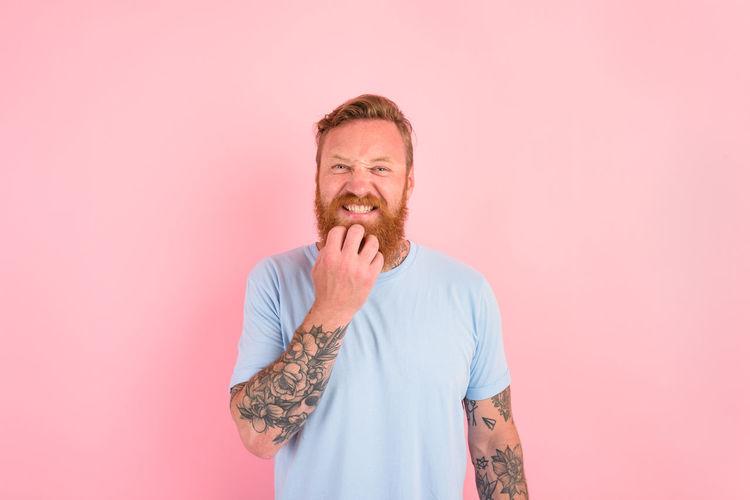 Midsection of man standing against pink background