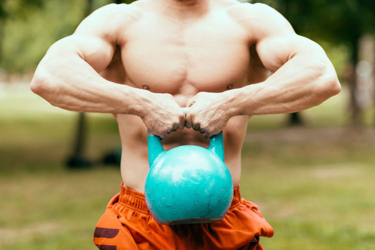Midsection Of Shirtless Man Lifting Kettlebell On Field