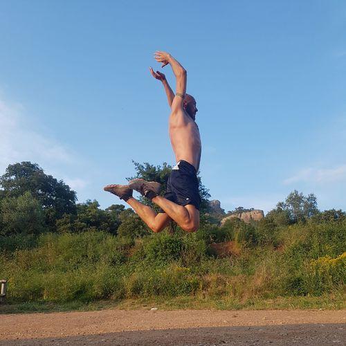 Full length of shirtless man jumping against sky