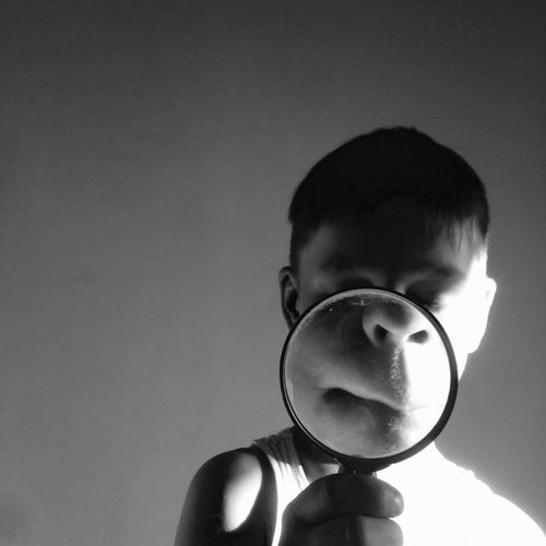 Boy holding magnifying glass against wall