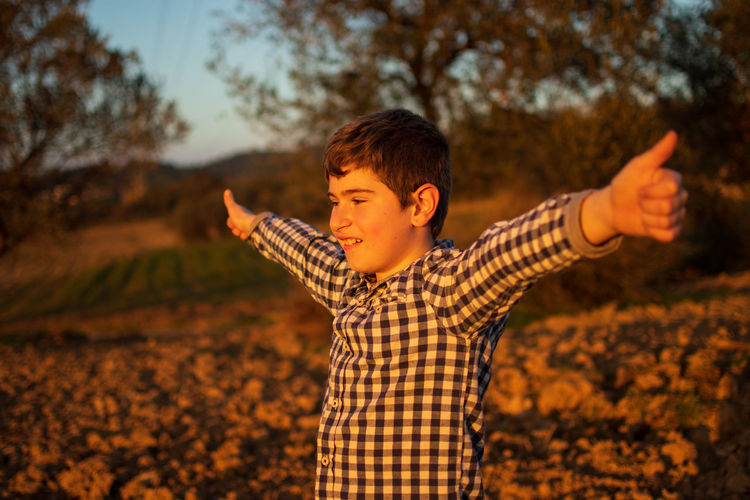 Smiling boy with arms outstretched standing on land during sunset