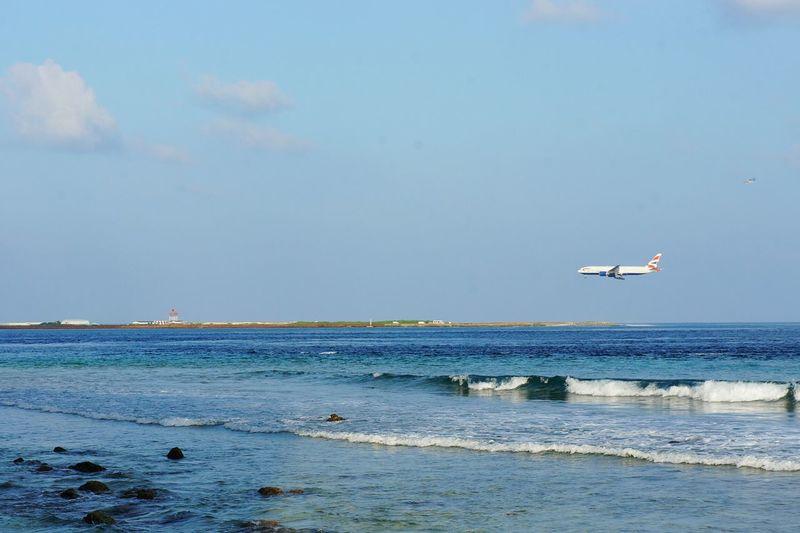 Plane landing on Ibrahim Nasir International Airport in North Male Atoll in Maldives Maldives Maldive Airport Aviation Landing Runway Airplane Plane Sealevel Rising Sinking Global Warming Male Sea Ocean Waves Flight Vacation
