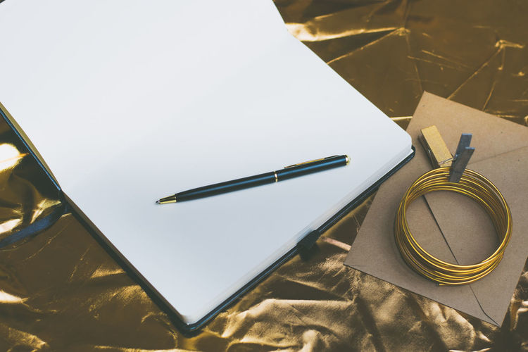 High angle view of blank book with pen on table