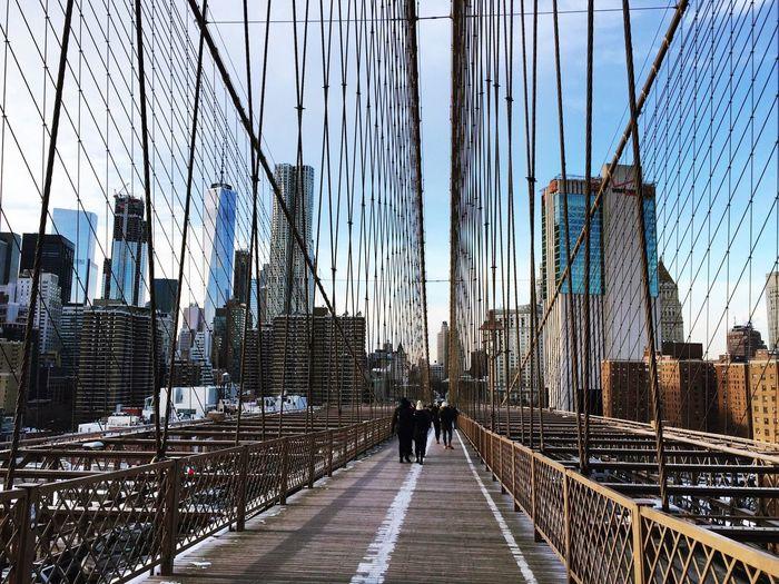 View of suspension bridge in city against sky