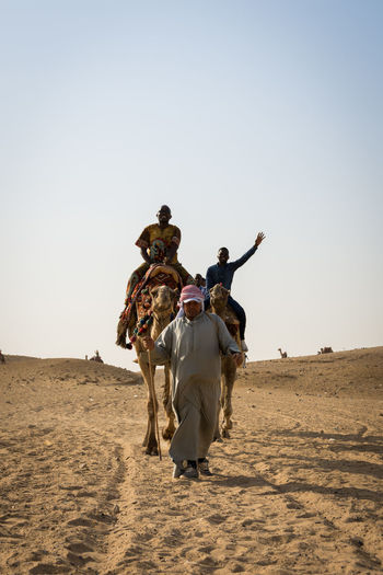 Men riding horse on sand against clear sky