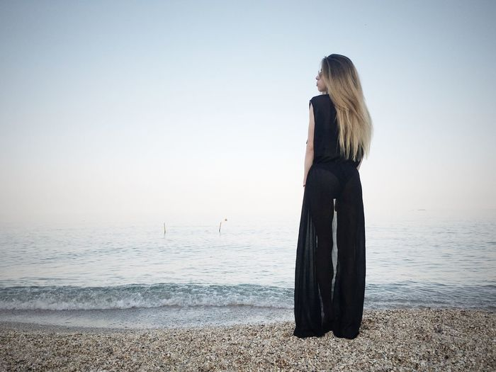 Full length of young woman wearing black dress while standing on shore at beach against sky