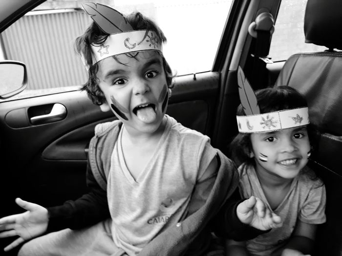 Portrait of siblings with face paint sitting in car