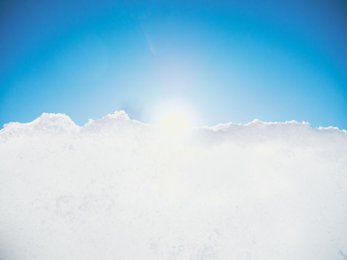 Low angle view of snow against blue sky
