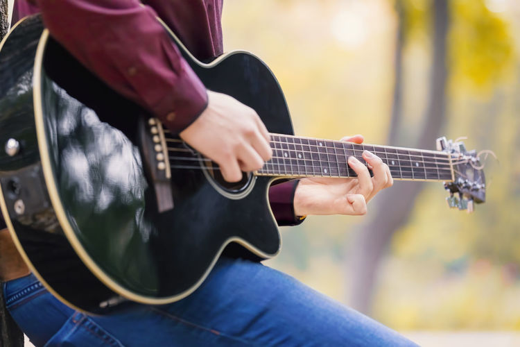Midsection of man playing guitar at park